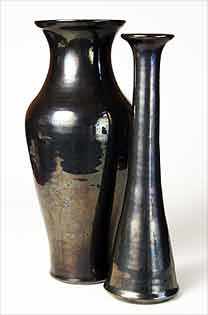 Two tall black vases